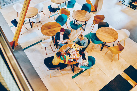 Top view of hipster students sitting at coffee table with laptop and sketches during collaboration on common task.Young people teamworking on development of studying project in cafe interior