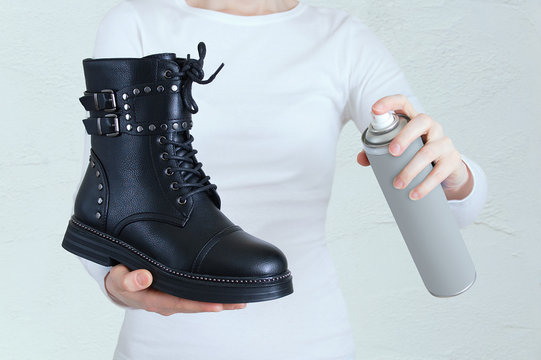 Leather shoe care. Black shoe and water-repellent spray for shoes in the hands of a Caucasian woman.