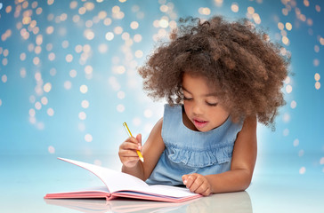 childhood, creativity, drawing and people concept - happy little african american girl with sketchbook and pencil over festive lights on blue background