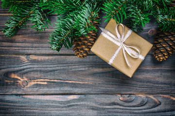 Wall Mural - Christmas composition background. Christmas gift with pine cones and fir branches on wooden background. Flat lay, top view, copy space. Toned