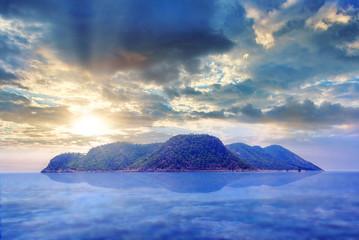 Einsame Insel im Ozean und Himmel mit Wolken und Sonnenstrahlen