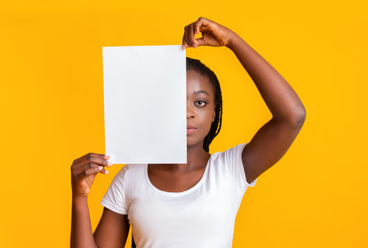 Serious girl covering half of her face with blank paper