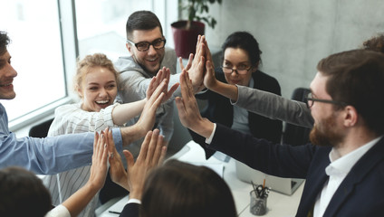 Motivated business team giving group high five
