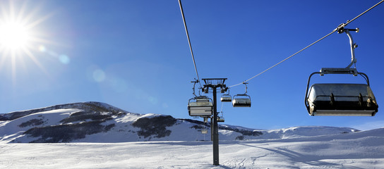 Fototapete - Chair-lift and blue sky with sun