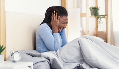 Black Girl Screaming Covering Ears Sitting In Bed At Home
