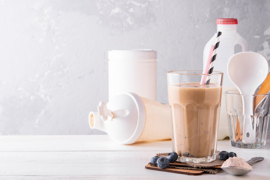 Chocolate protein shake on a white wooden background. Fresh milkshake with blueberry on a light table. A glass of chocolate smoothie .