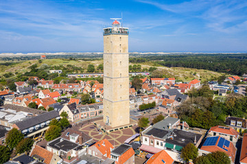 The tower of old Brandaris lighthouse among historical houses around the central square of West-Terschelling town. Terschelling island, West Frisian Islands, Dutch Wadden Sea, Netherlands