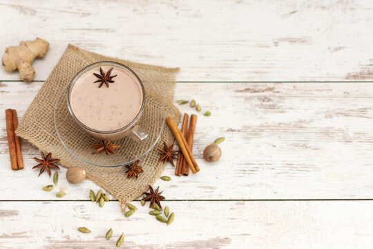 Masala chai made by brewing black tea with aromatic spices and herbs, such as Cinnamon Stick, Thai Cardamom, Ginger, Star Anise, Black Peppercorns and Black Tea top view.
