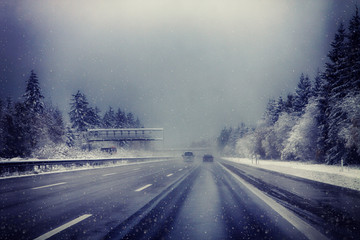 Germany, Bavaria, highway with rare traffic under snowstorm in winter
