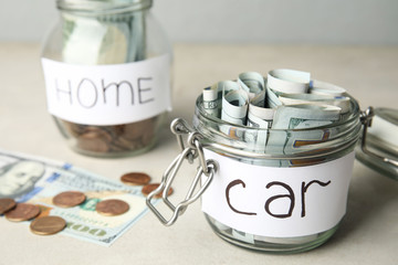 Glass jar with money and tag CAR on white table