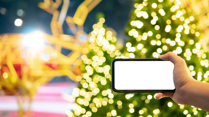 Male hand taking photo of illuminated Christmas tree and reindeer in Xmas holiday and New Year celebration event from smartphone. Mobile camera app for festive season. White blank device screen Wall mural