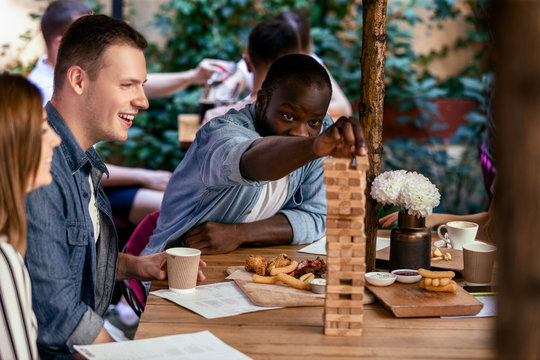 African boy is playing table game jenga with caucasian best friends at the local cozy restaurant