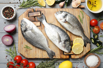 Flat lay composition with raw dorada fish on light grey wooden table