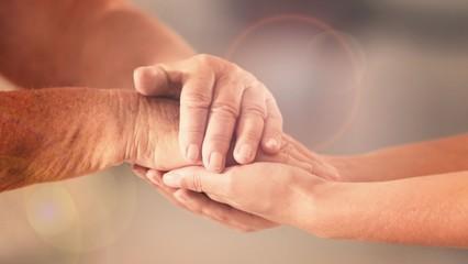 Volunteer and elderly woman holding hands in sunlit room, closeup