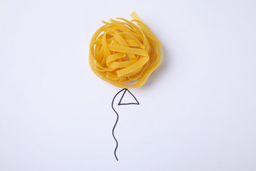 Balloon made with tagliatelle pasta on white background, top view