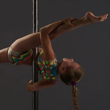 Adorable little girl exercising on pylon in studio