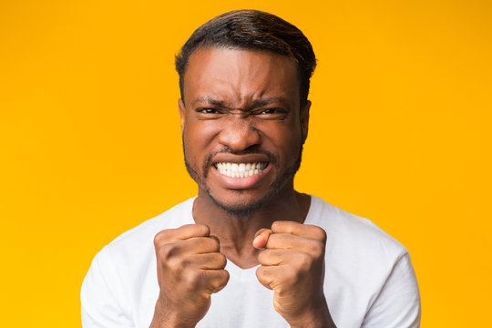 African American Guy Clenching Fists Looking At Camera, Yellow Background