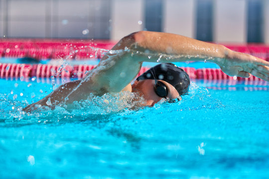 Swimmer man doing crawl swim in swimming pool portrait. Closeup of athlete wearing goggles, swimming cap training in blue water indoors.