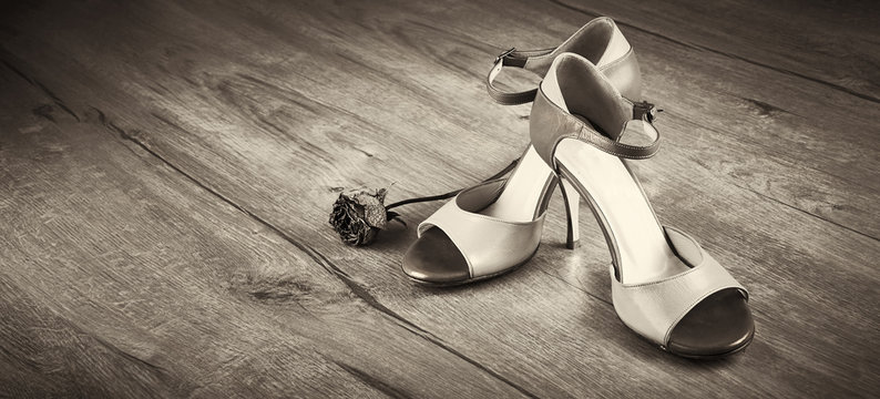 Panoramic toned close-up image of pair of female dancing shoes. Argentine tango shoes with dry rose on wooden floor. Sepia toned image with copy-space, place for your text.