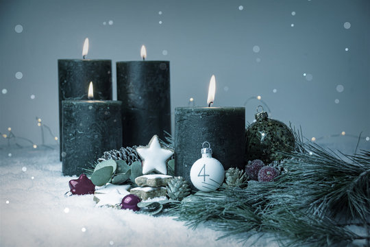 Fourth Advent - Burning Advent Candles in the snow - Christmas decoration