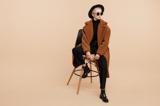 Serious young hipster woman with blonde short hair wearing a coat, hat and sunglasses posing over beige background.