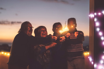Seniors friends having fun celebrating holidays together outdoor - Happy older people enjoying party laughing on terrace at sunset time - Elderly lifestyle activity and culture event concept