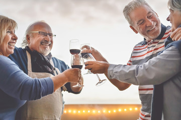 Happy seniors friends drinking red wine on terrace sunset - Mature people having fun laughing and sharing time together outdoor - Elderly retirement lifestyle activity  concept