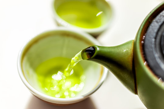 Closeup of green clay tea pot teapot on white table background and pouring liquid motion of colorful vibrant Japanese sencha or genmaicha drink during ceremony