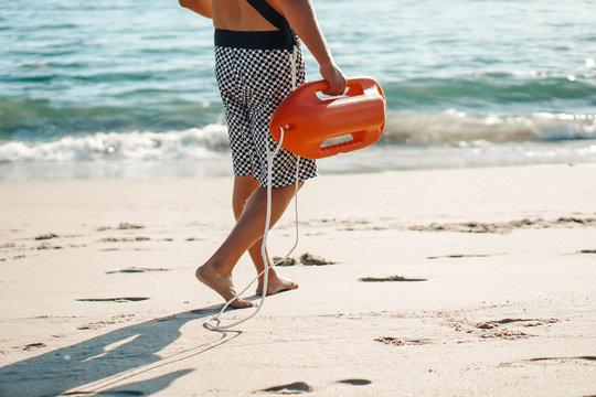 Male lifeguard running on the beach.