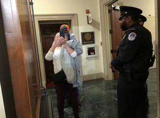 Tourists take picture through an open hearing room door after House Intelligence Committee hearing as part of the Trump impeachment inquiry in Washington