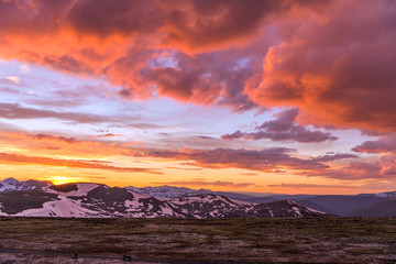 Foto auf Acrylglas Hochrote Spring Sunset at Top of Rockies - A wide-angle view of colorful Spring sunset clouds over snow-capped high peaks of the Continental Divide at top of Rocky Mountain National Park, Colorado, USA.