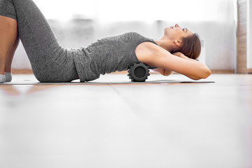 Girl doing yoga lying on massager on grey rug in gym