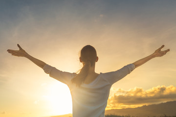 Happy young woman living arms put to sunset sky feeling good.