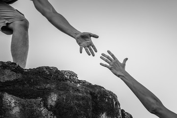 Fototapete - Hand reaching out for help up a mountain cliff.