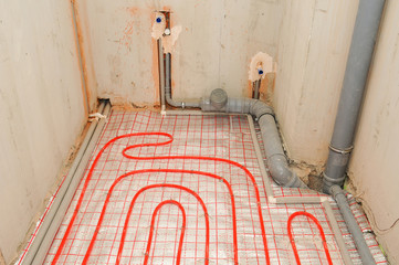 Installation water underfloor heating pipes on the silver reflective material in house construction.
