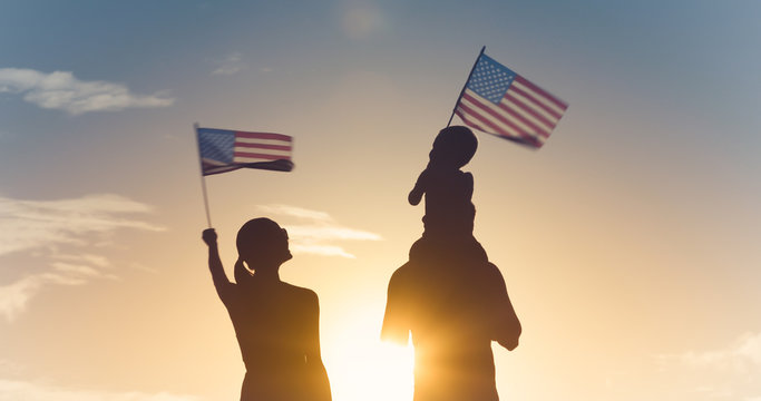 Patriotic man, woman, and child waving American flags in the air.