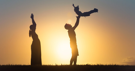 Family playing together having fun outdoors at sunset.