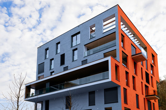 Colorful Modern residential apartment and flat building exterior in Salzburg, in Austria. New luxury house and home complex of blue and red color. City Real estate property and condo architecture.