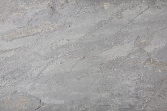 Close up of light grey textured slate tile background.