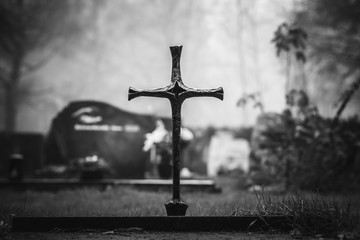 Vintage, retro photo of a cross above an old grave in an ancient cemetery. Grainy, noisy, artistic monochrome image. Halloween, all saints concept