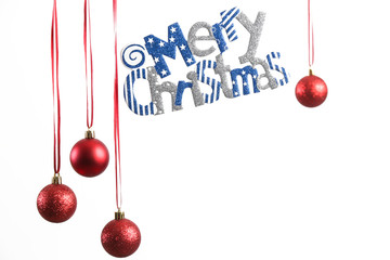 Red Christmas shiny balls and Merry Christmas sign hanging in front of white background.