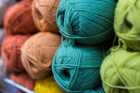 Colored skeins of wool on the shelf of the shop for needlework. Selection of colorful yarn wool on shopfront. Knitting background. Knitting balls of wool, crochet hooks pattern