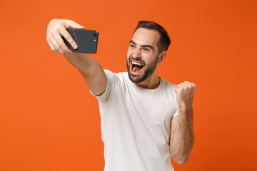 Happy young man in casual white t-shirt posing isolated on orange wall background studio portrait. People lifestyle concept. Mock up copy space. Doing selfie shot on mobile phone doing winner gesture.