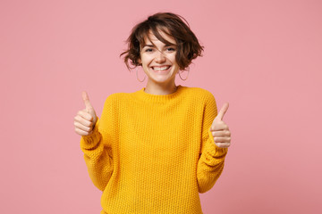 Cheerful young brunette woman girl in yellow sweater posing isolated on pastel pink wall background, studio portrait. People sincere emotions lifestyle concept. Mock up copy space. Showing thumbs up.