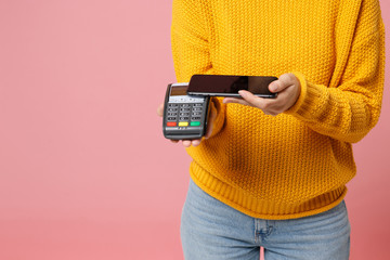 Cropped image of woman in yellow sweater posing isolated on pink background. People lifestyle concept. Mock up copy space. Hold payment terminal to process, acquire credit card payments, mobile phone.