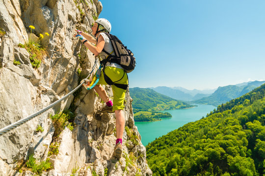 Beautiful young girl climbing Drachenwand via ferrata above scenic Mondsee lake, Alps, Austria, Europe