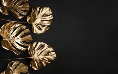 Trendy gold tropical monstera leaves on black background border frame