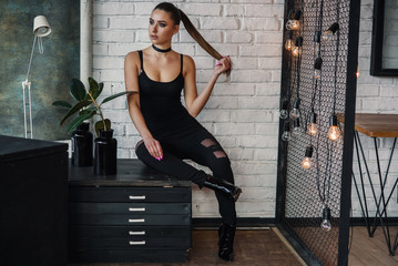 Beautiful fashionable woman at loft style room with white bricks wall and black iron net. Attractive girl with perfect figure in stylish black clothes.