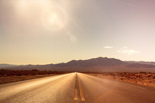 Desolate desert road with mountains with sunflare; western United Stated