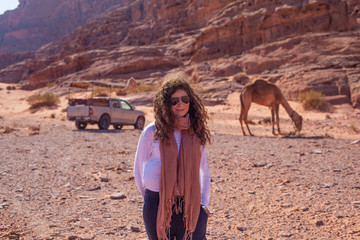 Woman posing in frond of a jeep and a camel in the Jordan desert